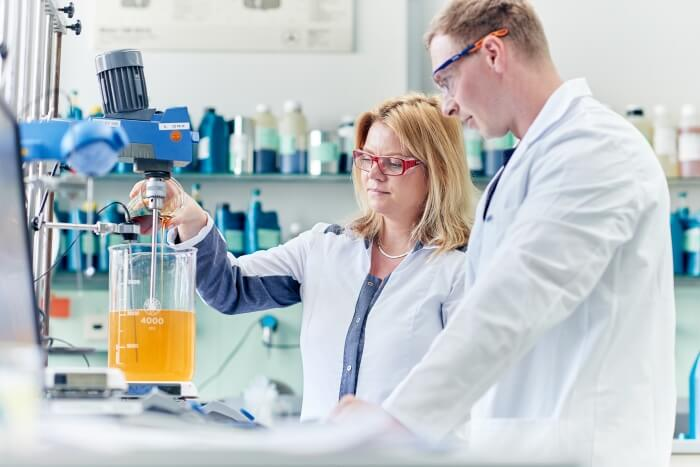 Two laboratory workers create engine oil