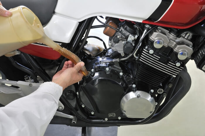 Someone fills motor oil in a motorcycle